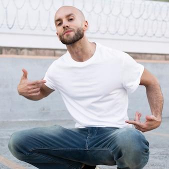 Homem vestido de forma casual sentado em uma sessão de fotos ao ar livre na calçada