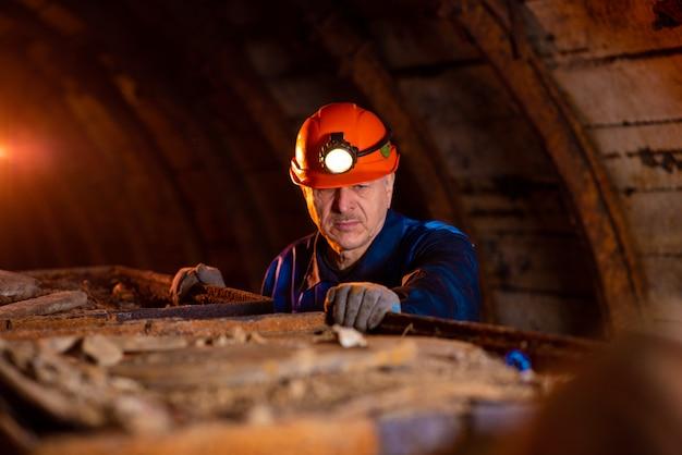Homem vestido de macacão de trabalho e um capacete dentro de uma mina