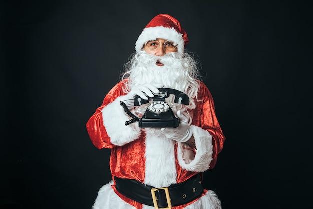 Homem vestido de papai noel segurando um telefone retrô dos anos 60, sobre fundo preto. conceito de natal, papai noel, presentes, celebração.