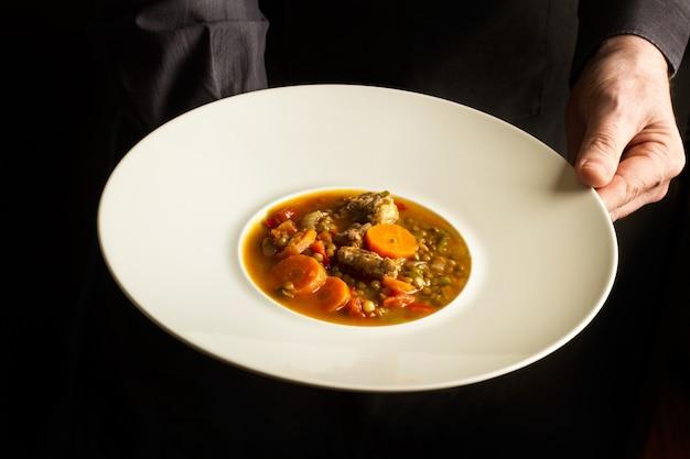 Homem vestido de preto segurando um prato fundo de cozido de lentilhas