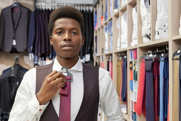 Homem vestindo camisa branca, colete preto, escolhendo a gravata.