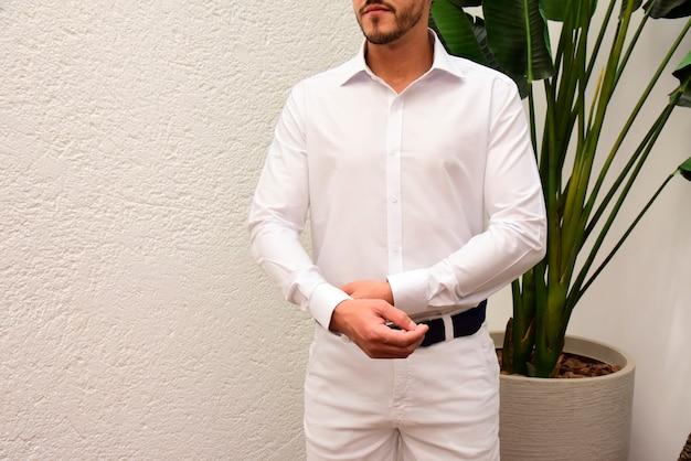 Homem vestindo camisa branca e calça branca com faixa preta