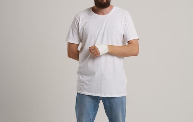 Homem vestindo camiseta branca paciente enfaixado mão problemas de saúde pronto-socorro