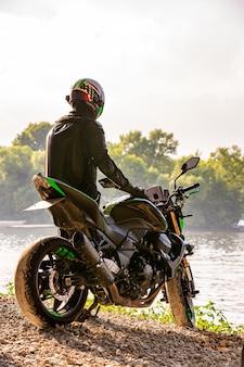 Homem vestindo capacete de motocicleta e uniforme de segurança, sentado na bicicleta ao ar livre, bela paisagem cênica