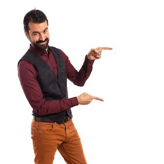 Homem vestindo colete apontando para o lateral