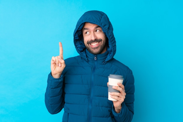 Homem vestindo jaqueta de inverno e segurando um café para viagem sobre parede azul isolada, com a intenção de realizar a solução enquanto levanta um dedo