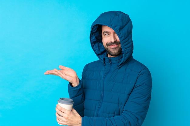 Homem vestindo jaqueta de inverno e segurando um café para viagem sobre parede azul isolada, estendendo as mãos para o lado para convidar para vir