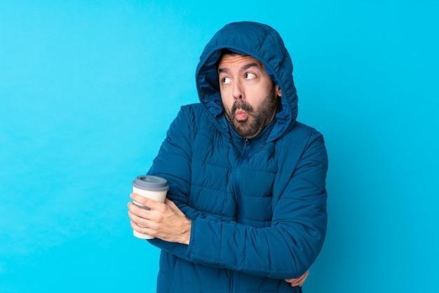Homem vestindo jaqueta de inverno e segurando um café para viagem sobre parede azul isolada, fazendo dúvidas gesto enquanto levanta os ombros