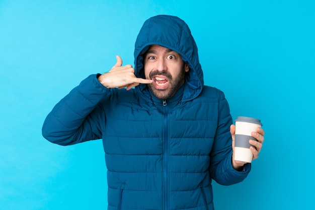 Homem vestindo jaqueta de inverno e segurando um café para viagem sobre parede azul isolada, fazendo gesto de telefone e duvidar