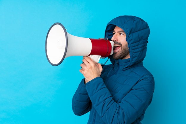 Homem vestindo jaqueta de inverno e segurando um café para viagem sobre parede azul isolada gritando através de um megafone