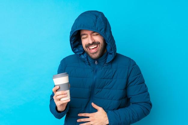 Homem vestindo jaqueta de inverno e segurando um café para viagem sobre parede azul isolada, sorrindo muito