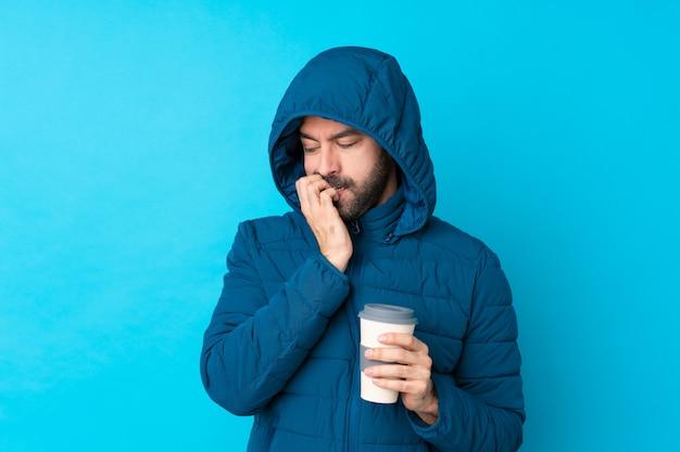 Homem vestindo jaqueta de inverno e segurando um café para viagem sobre parede azul isolada, tendo dúvidas