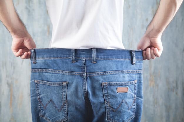 Homem vestindo jeans grande. perda de peso
