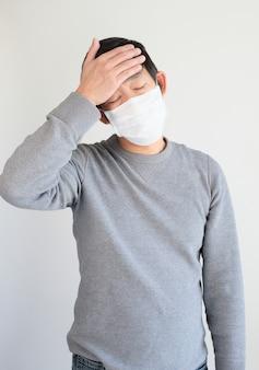 Homem vestindo máscara protetora com dor de cabeça