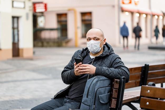 Homem vestindo máscara protetora segurando um smartphone.