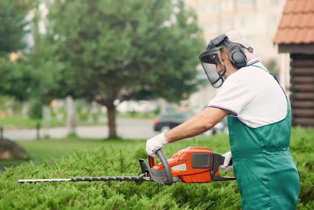 Homem vestindo orelha e rosto defensores cortando arbustos.