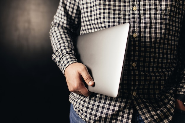 Homem vestindo roupas casuais segurando laptop fechado, fundo preto desfocado