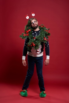 Homem vestindo roupas de natal e uma guirlanda
