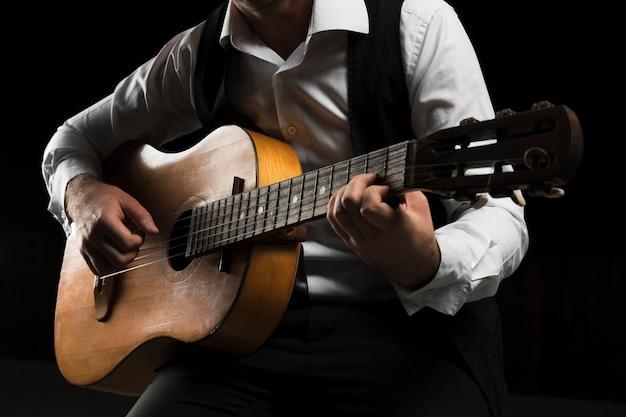Homem vestindo roupas de palco tocando guitarra