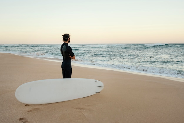 Homem vestindo roupas de surfista observando o nascer do sol