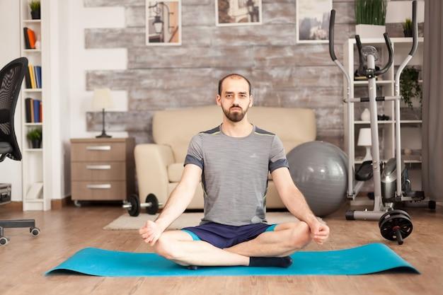 Homem vestindo roupas esportivas enquanto faz a pose de lótus ioga na esteira em casa e a bola suíça no fundo em tempo de isolamento covid-19.
