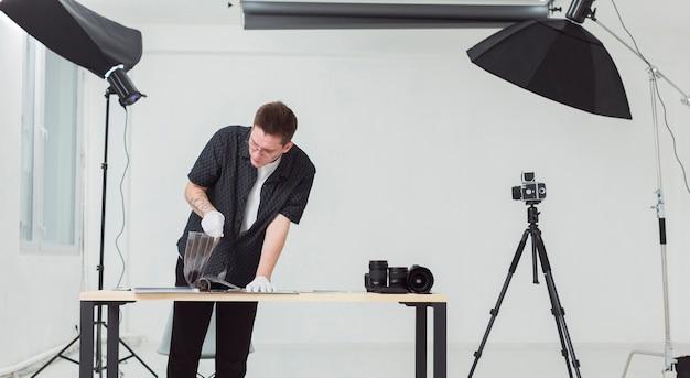 Homem vestindo roupas pretas, trabalhando em seu estúdio de fotografia