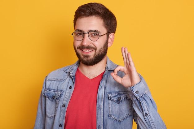 Homem vestindo roupas stylich fazendo sinal de ok e olhando sorrindo, cara vestida jaqueta jeans e camiseta vermelha