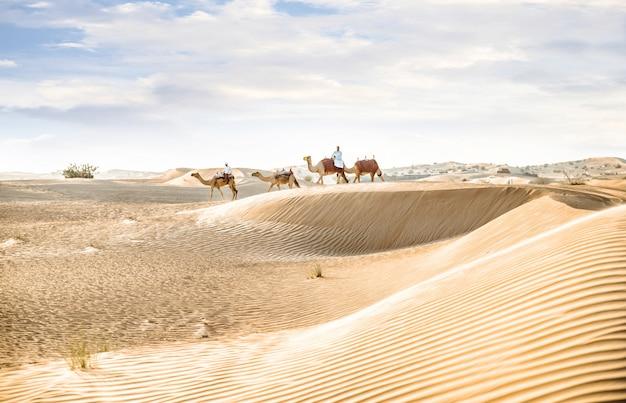 Homem vestindo roupas tradicionais, tirando um camelo na areia do deserto, em dubai