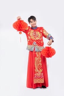 Homem vestindo terno cheongsam mostra decoração de lâmpada vermelha em sua loja no ano novo chinês