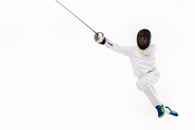 Homem vestindo terno de esgrima a praticar com espada contra cinza