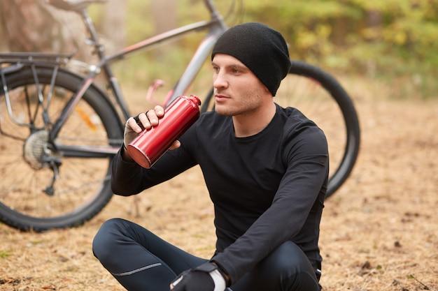 Homem vestindo terno preto e boné, sentado ouvir sua bicicleta onground e beber água de garrafa vermelha no parque ou floresta, desportivo masculino olhando para a frente, descansar depois de longas horas de equitação.