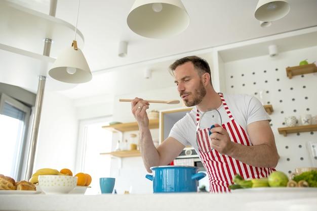 Homem vestindo um avental branco com linhas vermelhas e cozinhando algo na cozinha