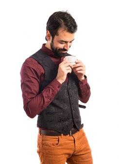 Homem vestindo um chaleco bebendo café