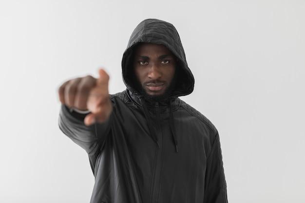 Homem vestindo um moletom e apontando o dedo