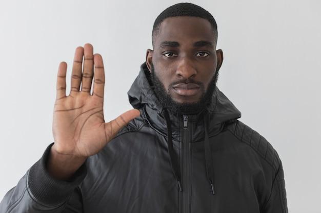 Homem vestindo um moletom e mostrando a mão