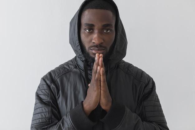 Homem vestindo um moletom e orando