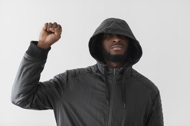 Homem vestindo um moletom e segurando o punho no ar