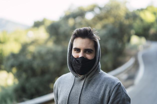 Homem vestindo um suéter e uma máscara facial em uma estrada
