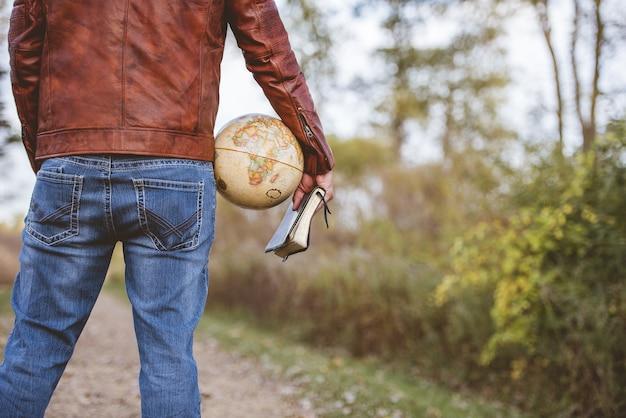 Homem vestindo uma jaqueta de couro e jeans segurando um globo de mesa e a bíblia