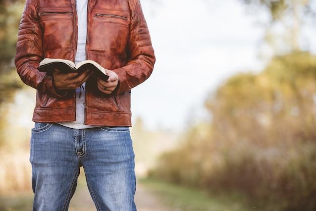 Homem vestindo uma jaqueta de couro em uma estrada vazia e lendo a bíblia com o espaço desfocado