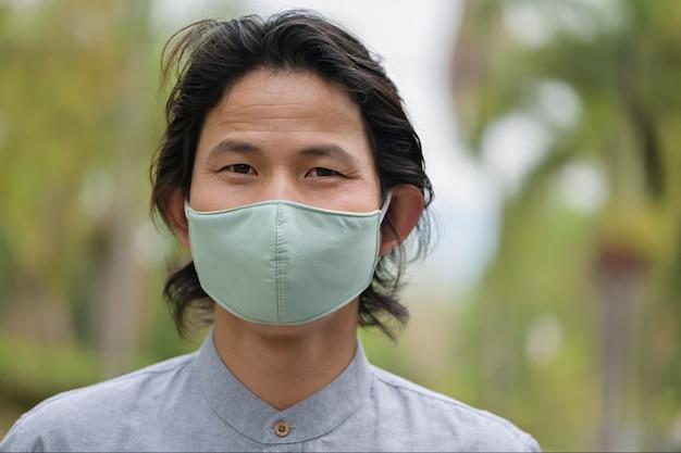 Homem vestindo uma máscara de pano em área pública se proteger do risco de doença