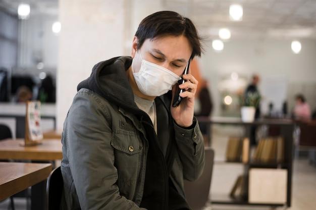 Homem vestindo uma máscara médica e falando ao telefone
