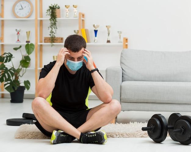 Homem vestindo uma máscara médica enquanto vestindo roupas esportivas