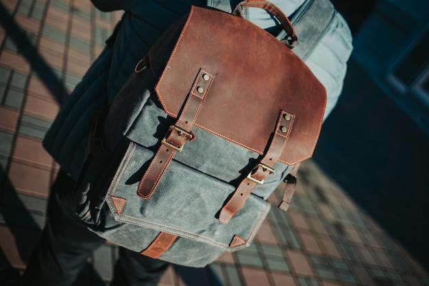 Homem vestindo uma mochila cinza e marrom