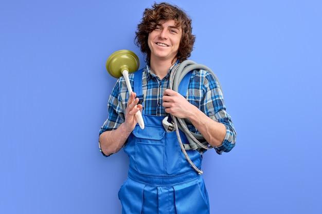 Homem vestindo uniforme de encanador segurando o êmbolo do vaso sanitário e comemorando a conquista com um sorriso feliz