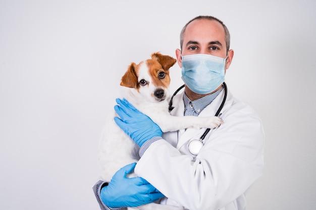 Homem veterinário trabalhando na clínica com cão pequeno bonito jack russell.