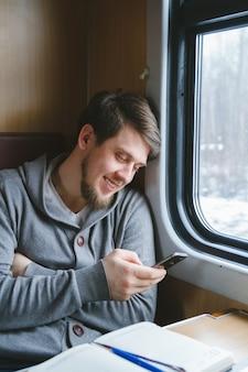 Homem viaja de trem sentado perto da janela usando telefone celular
