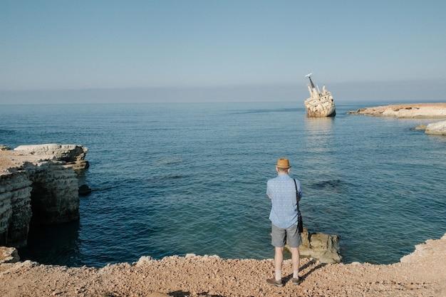 Homem viajando perto do oceano em chipre. férias de verão do conceito de estilo de vida de homem ao ar livre. bela paisagem natural na vista traseira do fundo