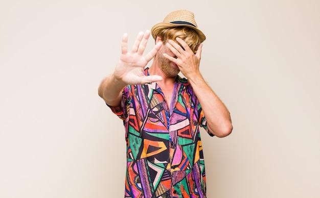 Homem viajante adulto loiro cobrindo o rosto com a mão e colocando a outra mão na frente para parar a câmera, recusando fotos ou imagens