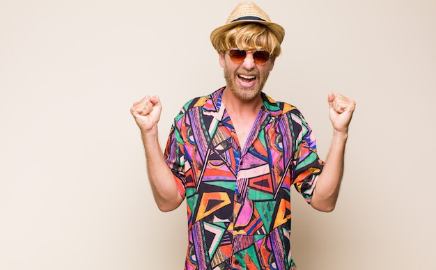 Homem viajante adulto loiro parecendo extremamente feliz e surpreso, comemorando o sucesso, gritando e pulando